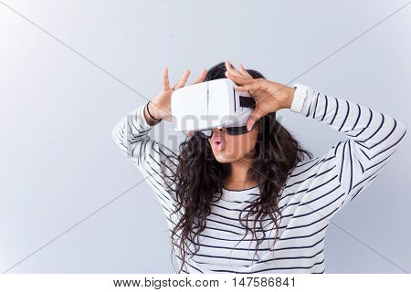 Full of emotion. Positive content emotional woman using virtual reality device while standing isolated o grey background