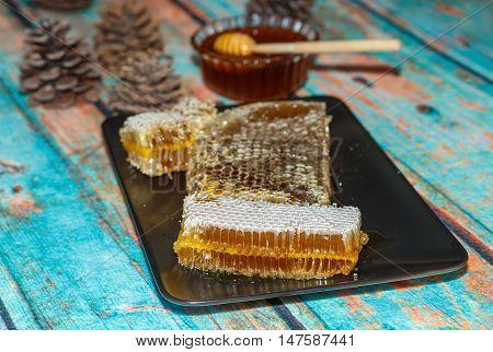 Famous Marmaris (Turkey) pine honey comb and liquid honey on surface imitating wood with cones. Photo toned