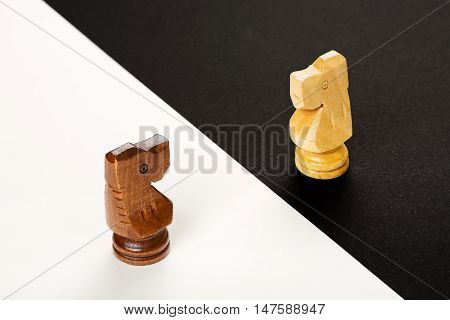 wooden chess knights on black and white background abstract concept