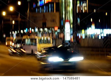 Cars go on night city street. Abstraction