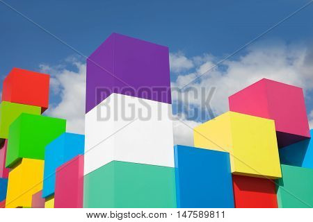 colorful cubes against blue sky and white clouds. Yellow, red, green, blue, pink colored blocks.