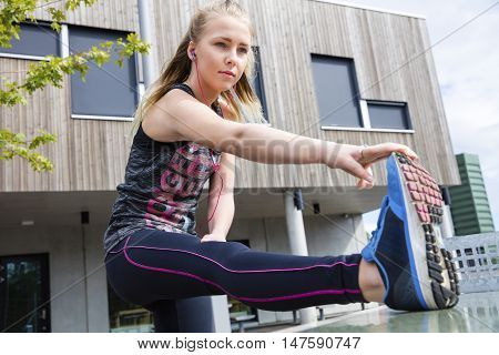 Determined young woman in sportswear stretching her leg against building