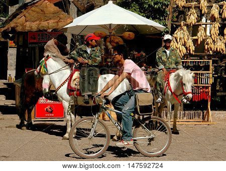 Shu He China - April 26 2006: Man on a bicycle passes two Naxi carriage drivers seated on their minature white horses