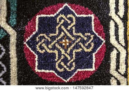 Pattern cross from ethnic symbol of eternity on  border of the carpet