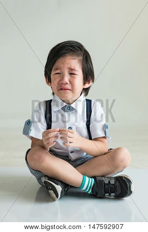 Close up of sadness asian boy sit and crying on the ground.