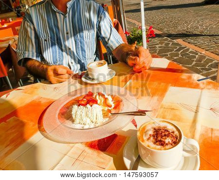 The dessert strawberries with cream and cup of coffe on the table of the outdoor cafe on the italian sidewalk. Taken during Italian vacation.