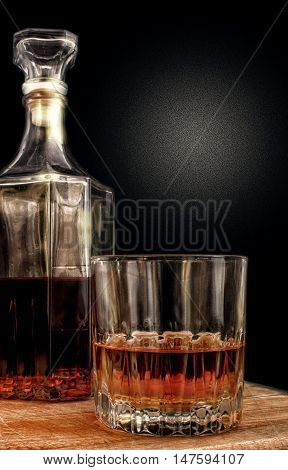 Glass with alcohol against a dark background with a gradient. On a background - a decanter. Vertical format. Indoors. Color. Photo.