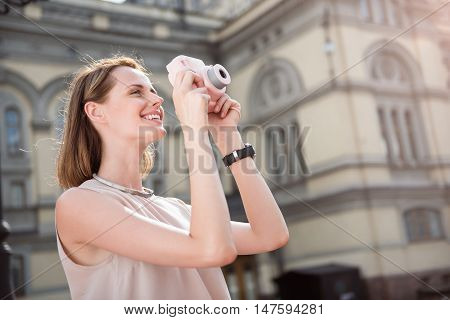 Unforgettable. Positive young woman using the camera while traveling in the city
