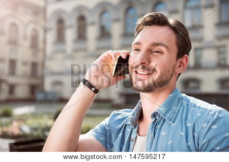 Nice talk. Portrait of cheerful man talking on the phone