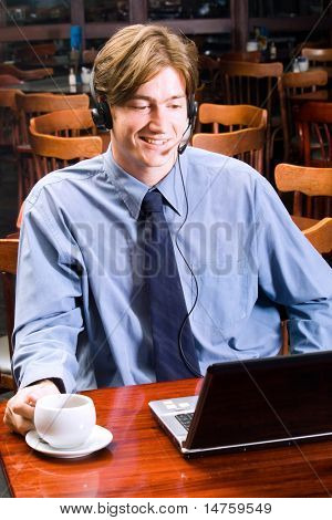 handsome young businessman talking to someone over internet communication device using headset