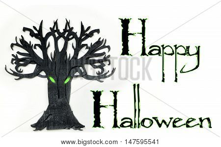 A wooden cutout of bare tree shape painted black. The rough texture of the wood is showing through the black paint. The tree has glowing green eyes. Happy Halloween text added