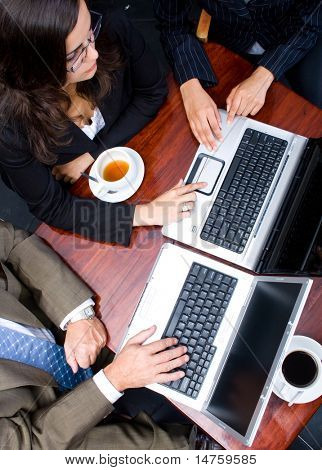 Overhead view of three business people meeting in a cafe