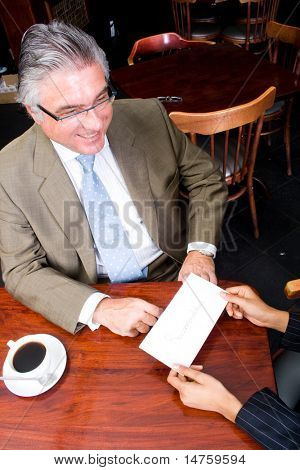 a business woman handing in a letter of resignation to her boss