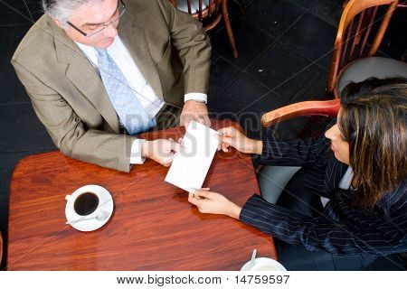 A businesswoman handing in a blank envelope to her boss