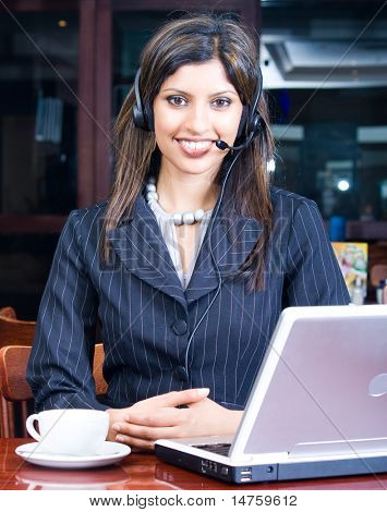 closeup of smiling indian business woman with headset and laptop in a cafe