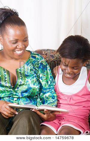 a happy african mother reading a book to her daughter