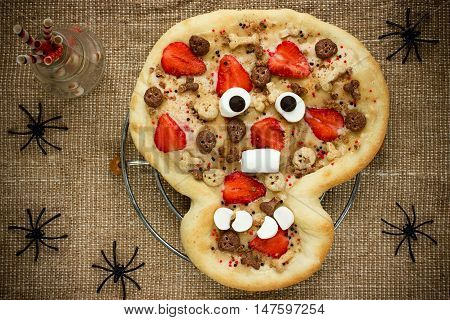 Sweet pizza in the form of funny skull to treat kids at Halloween party top view