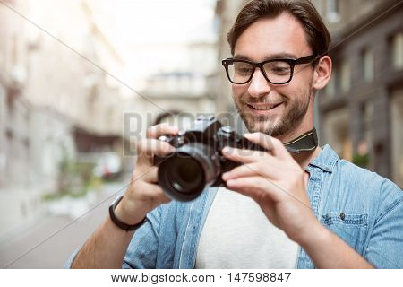 Urban photoshoot. Pleasant good looking joyful photographer holding his camera and smiling while looking at the photos