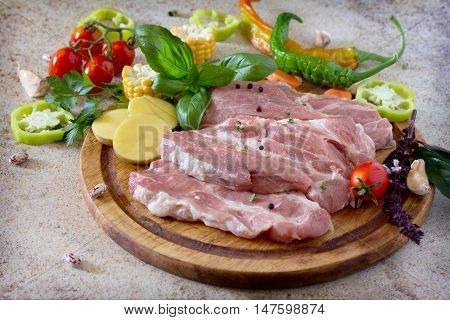 Fresh Raw Meat Pork Tenderloin With Vegetables On A Cutting Board. Stone Background.