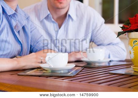 young couple drinking coffee in open-air cafe