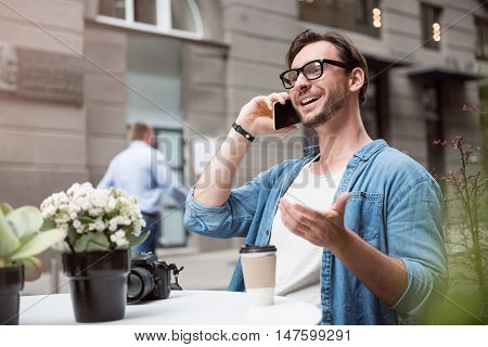 Pleasant conversation. Young delighted optimistic man speaking on the cellphone and smiling while sitting at the table