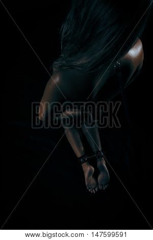 Low key photo of sexy female nude back and hands binded with cuffs and collar holding whip against dark background overhead view