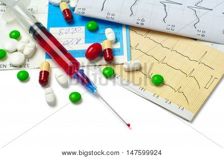 Syringe electrocardiogram and tablets on white background