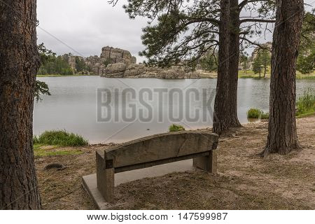 A park bench facing a scenic lake.