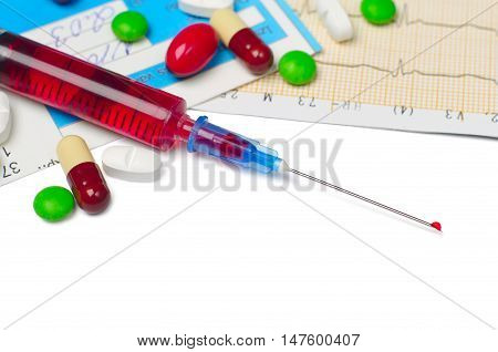 Medical syringe electrocardiogram and tablets on white