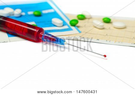Medical syringe and tablets on white background