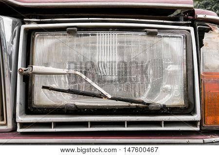 Close up a headlight with a wiper detail on old car