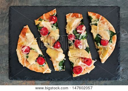 Flat bread pizza with melted mozzarella tomatoes spinach and artichokes overhead view on slate