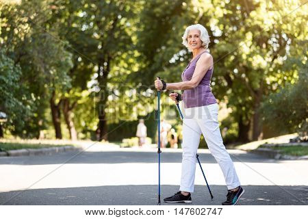 Good morning Smiley lady having her exercises with walking sticks