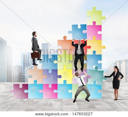 Team holds a puzzle as a scale to climb a man