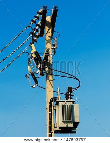high-voltage transformer near building on blue sky background