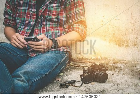 Young Man Using Mobile Phone with old retro camera
