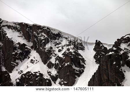 Rocks With Snow Cornice In Gray Day