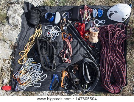 Climbing gear laid out on a stone in front of the ascent.