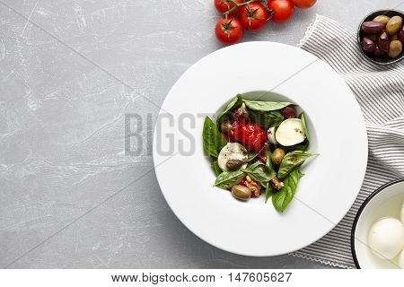 Italian salad with fresh basil leaves, olives, capers, walnuts, mozzarella cheese and red pepper on stone background.