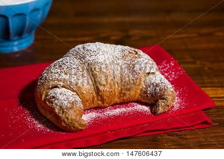 Croissant over a red napkin and a blue mug on background