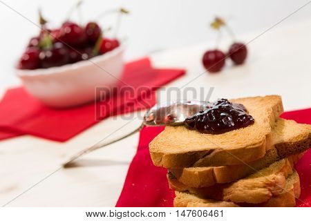 Closeup of rusk with cherry jam and cherry fruit on background