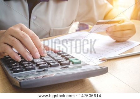 Close up hands holding a credit card and using calculator for online shopping
