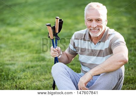 Have some rest. Grey man with hazel eyes posing while sitting on green grass with tracking sticks in his habds