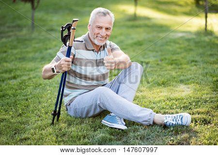 Thumb up Retiree enjoying himself after a good walk in summer park