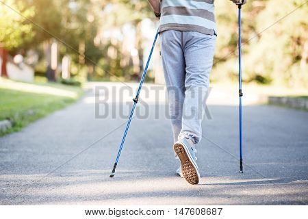 Achieving. Horizontal view of male legs while having a walk outdoors with tracksticks