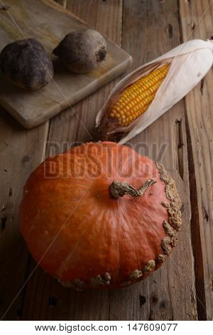 Still life of pumpkin, maize and beet on wooden old table.