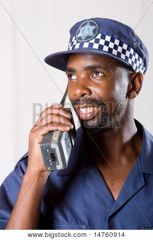 african policeman using walkie-talkie