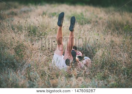 Young couple fools around in the field kicking up his feet