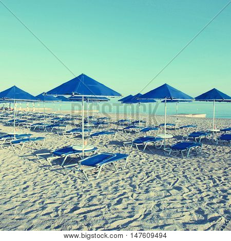 Blue umbrellas and chaise longue on empty sandy beach in the morning, Crete, Greece. Square toned image, instagram effect