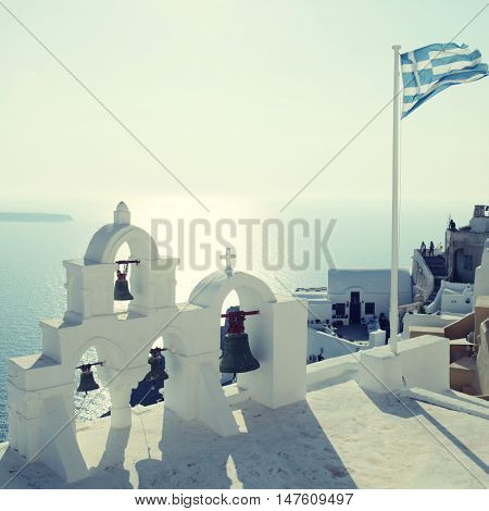 Sunset sea view with Greek flag and bell tower in Oia village, Santorini, Greece. sqauare toned image, instagram effect